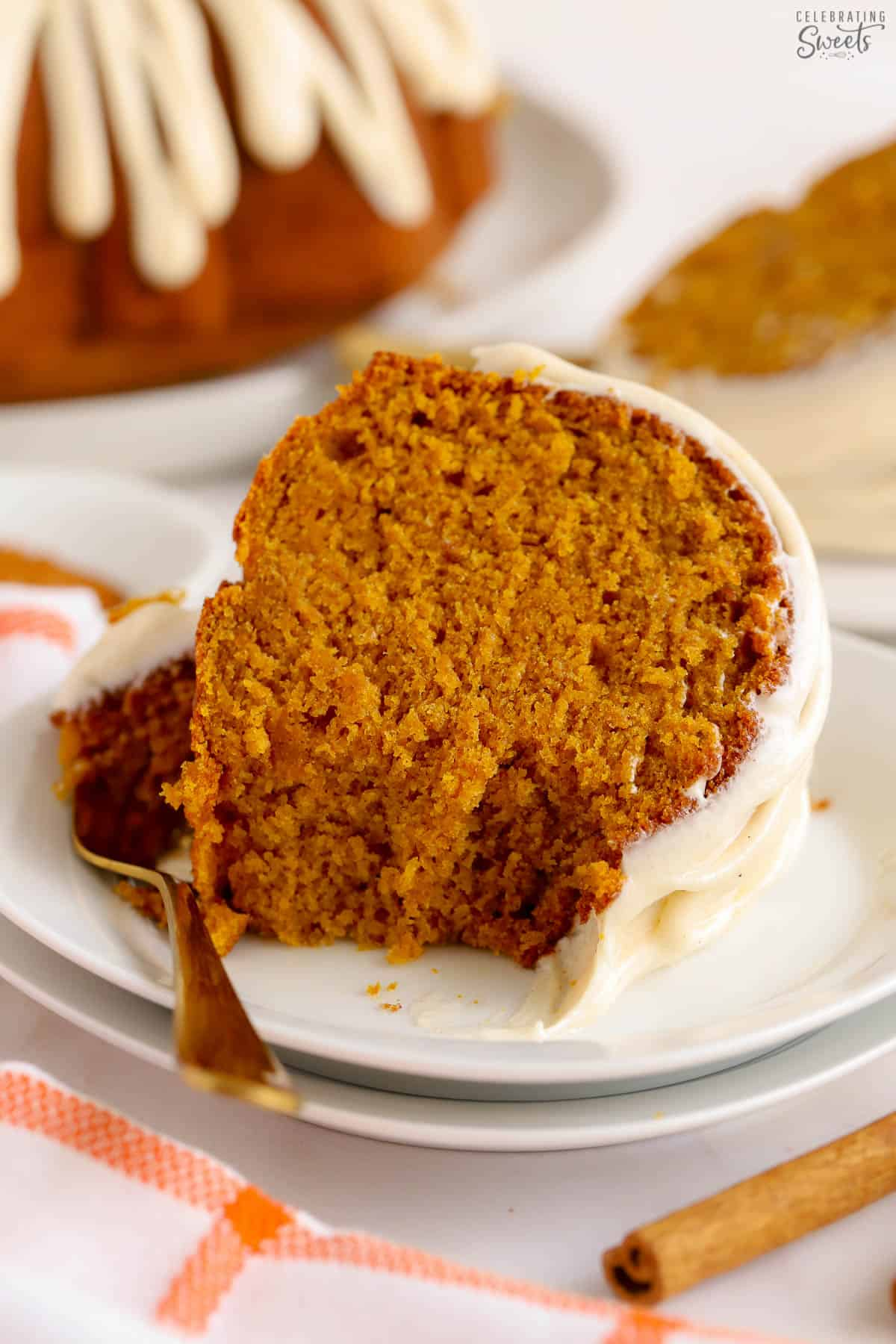 Slice of pumpkin bundt cake on a white plate with a gold fork.