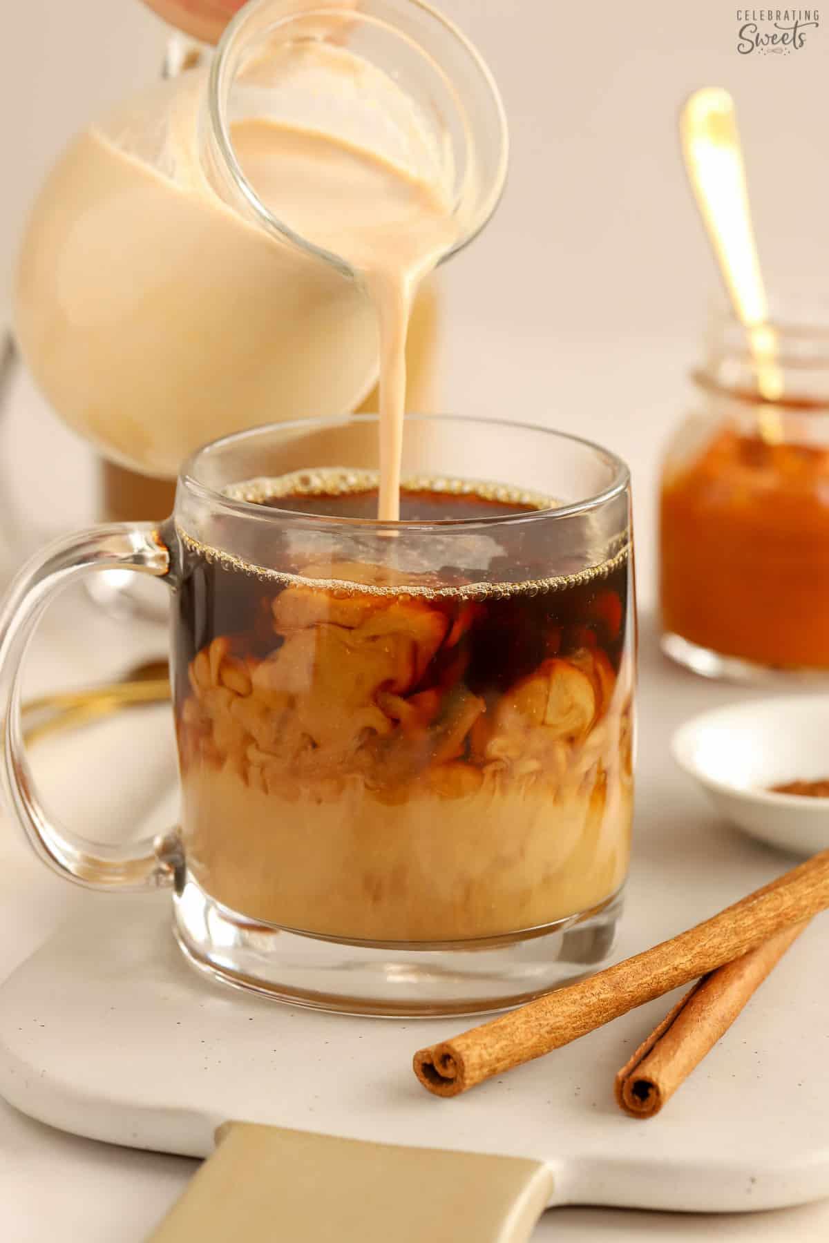 Pumpkin spice creamer being poured into a mug of black coffee.