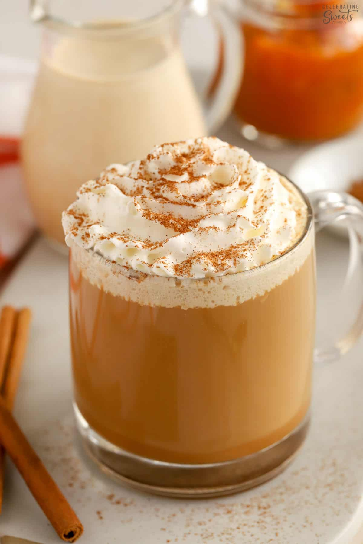 A cup of coffee topped with whipped cream and cinnamon.