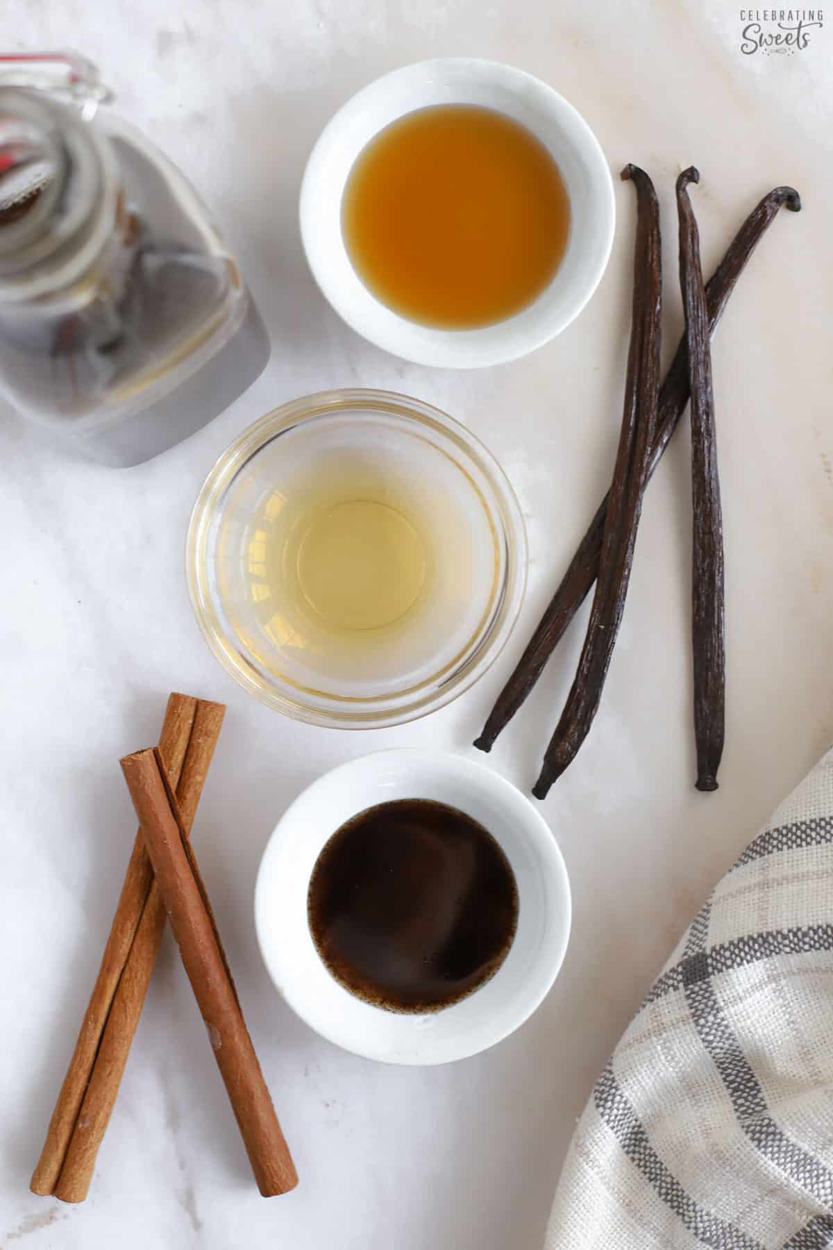 Vanilla beans, cinnamon sticks, and extracts in small bowls.