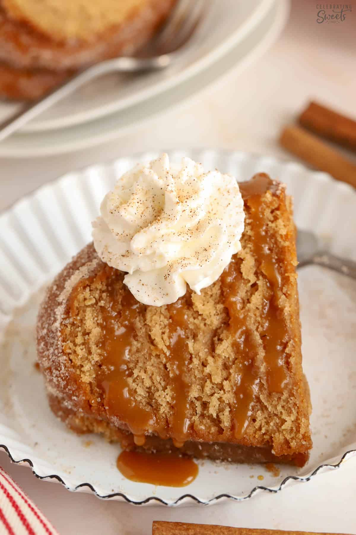 Slice of apple cider donut cake drizzled with caramel sauce and topped with whipped cream.